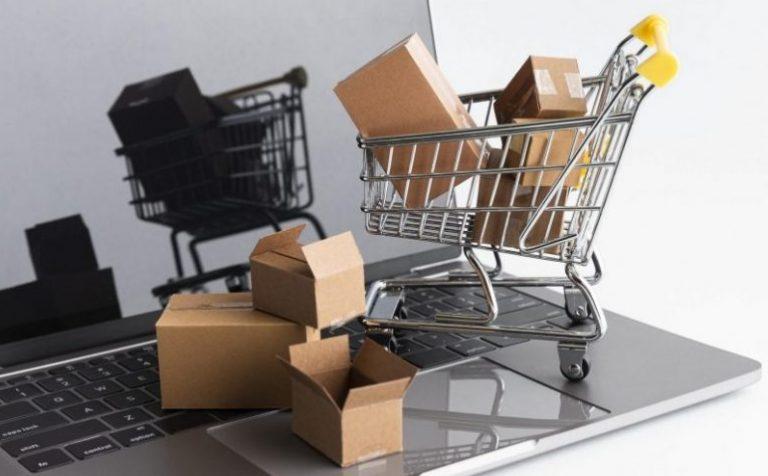 Um notebook aberto em fundo branco com um carrinho de compras cheio de caixas de papelão faz referência ao aumento de vendas em loja online.