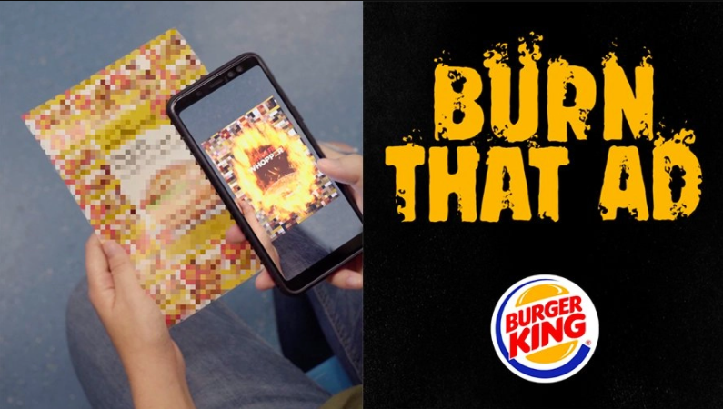 Someone points a cellphone to a burguer ad that is digitally burned on the screen.