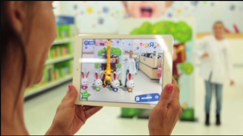 A mother holds a tablet in her hands to take pictures of her daughter and rabbits generated with augmented reality.
