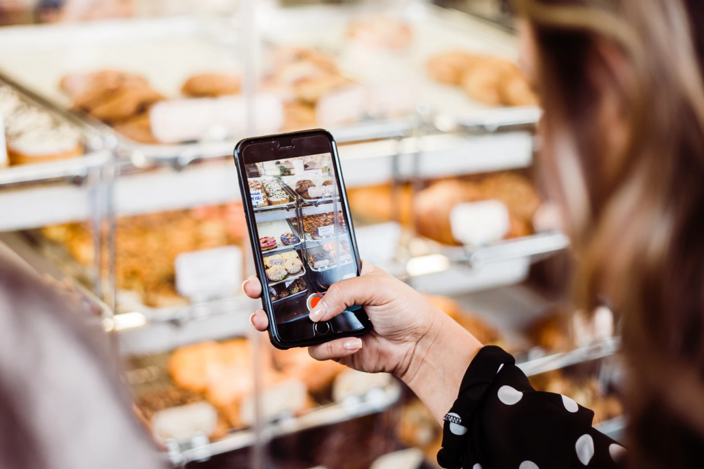 Person engaging with a mobile experience at a local bakery. Source: Unplash.