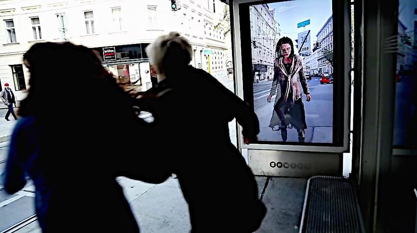 Duas senhoras se assustam com o movimento de um zumbi que aparece em uma tela instalada estação de bondinho. Com o recurso de Realidade Aumentada,  simula realisticamente estar do outro lado.