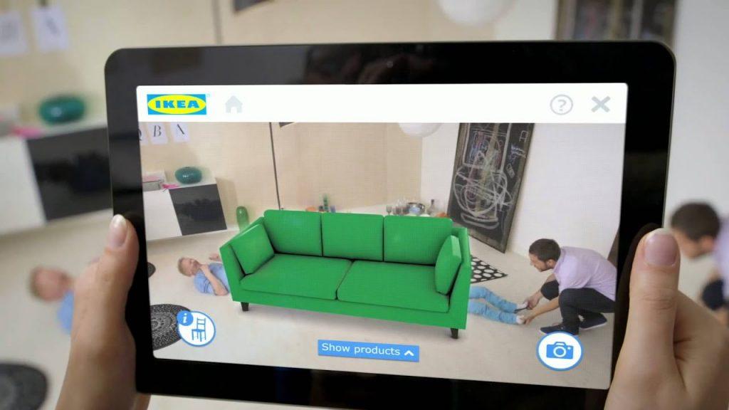 Mãos femininas seguram um tablet que mostra em sua tela três pessoas simulando uma cena com a ajuda da projeção de um sofá virtual verde da empresa.