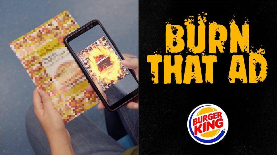 Um celular é apontado para um panfleto do McDonald's e, com a ajuda de um app de Realidade Aumentada, vê-se o panfleto queimar, apresentando uma promoção do Burger King em seu lugar.
