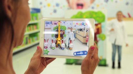 Mãe segura um tablet apontando-o para sua filha, que dança junto com as figuras animas visualizadas na tela, com Realidade Aumentada.