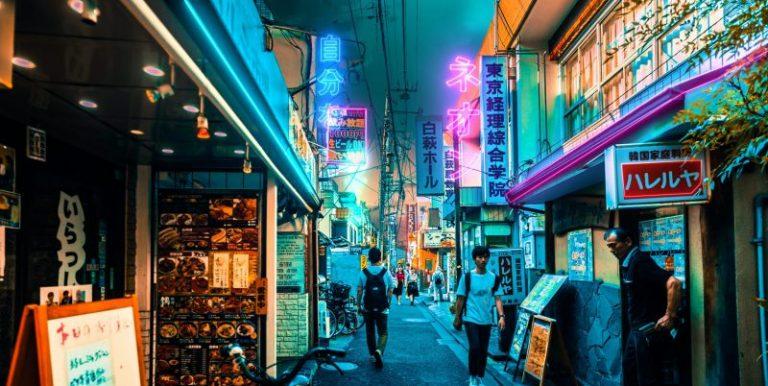 Foto de uma rua coreana a noite, mostrando pedestres entre placas iluminadas que se assemelham à Realidade Aumentada promocional   Foto por Jezael Melgoza, disponível em: Unsplash.com