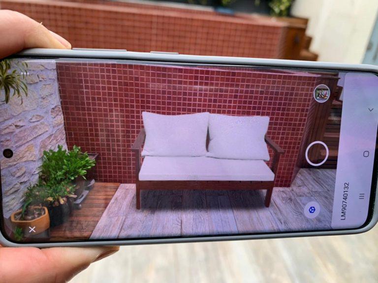 uma mão segura um celular que projeta um sofá para área externa no ambiente com o uso da web AR