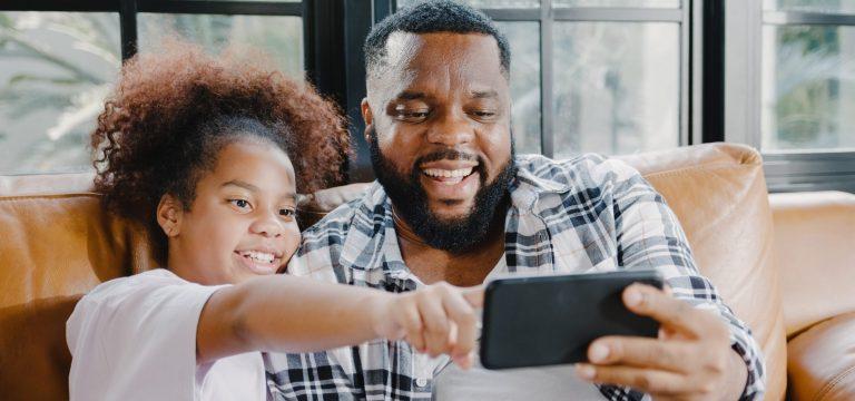 Homem preto e sua filha sentados em um sofá experimentam a Realidade Aumentada em seu celular, fazendo referência aos diferentes papeis de Comprador e de Consumidor. Adaptado de foto de: tirachardz. Disponível em: www.freepik.com.
